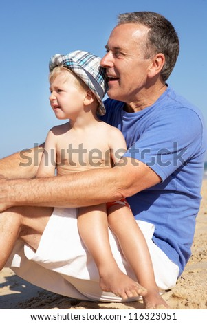 Grandfather And Grandson Sitting On Beach - stock photo