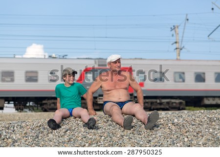 grandfather and grandson sitting on the railway embankment - stock photo