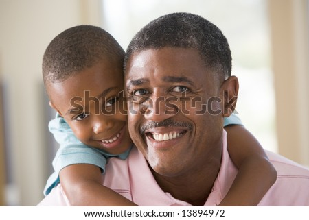 Grandfather and grandson smiling - stock photo