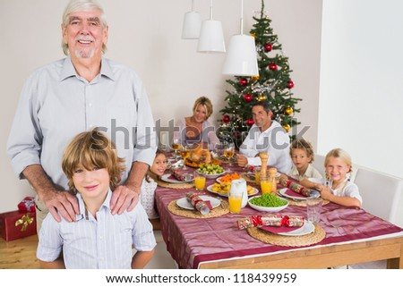 Grandfather and grandson standing beside the dinner table at christmas time