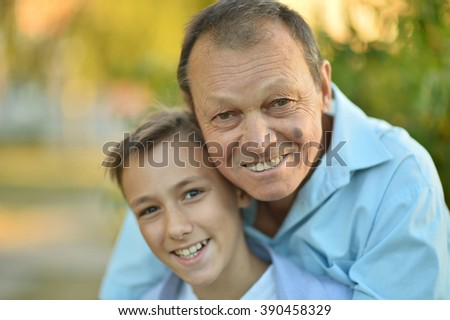 Grandfather and grandson together in autumn park - stock photo