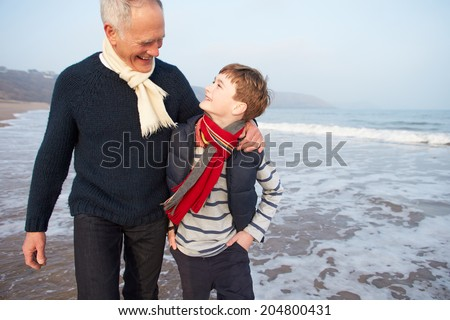 Grandfather And Grandson Walking On Winter Beach - stock photo