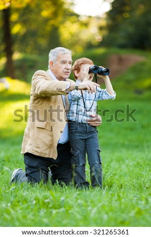 Grandfather and grandson watching nature with binoculars in park - stock photo