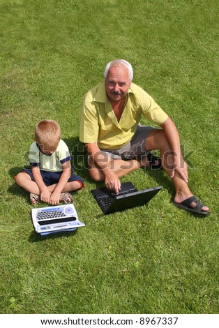 Grandfather and grandson working on laptops - stock photo