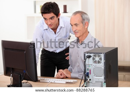 grandfather and grandson working together on a computer