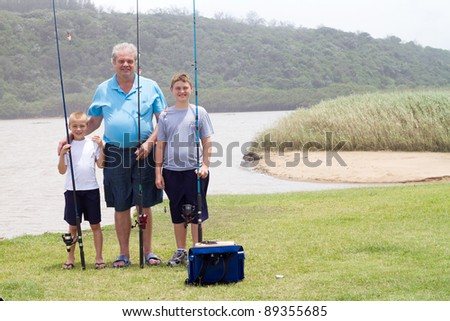 grandfather and grandsons fishing by the lake - stock photo