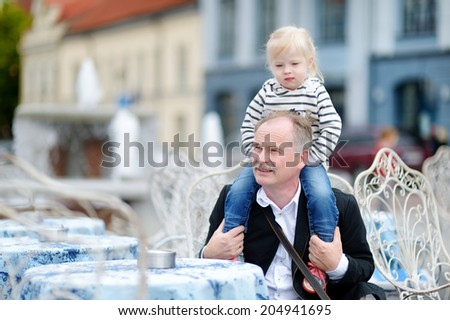 Grandfather and his grandchild at summer cafe on beautiful sunny day - stock photo