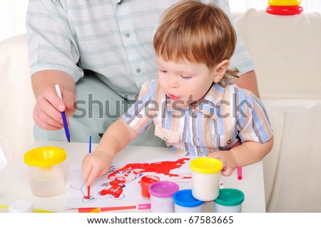 Grandfather and his grandson involved in drawing together. Symbol of the family.