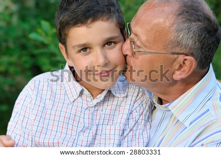 Grandfather and kid outdoors - stock photo