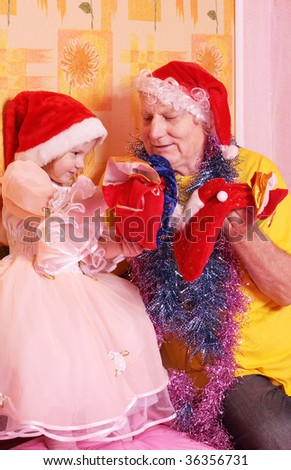 grandfather and little girl in red christmas hat - stock photo