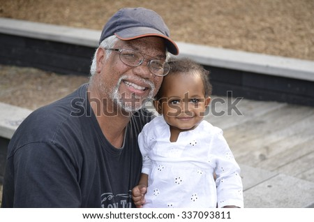 Grandfather and toddler girl at the park - stock photo