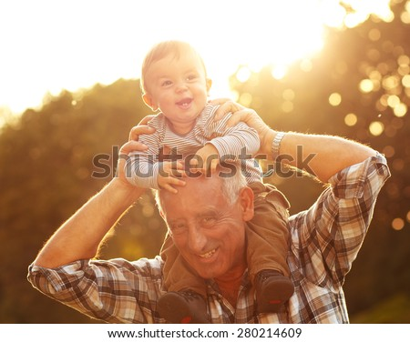 Grandfather carrying grandson on shoulders in park - stock photo