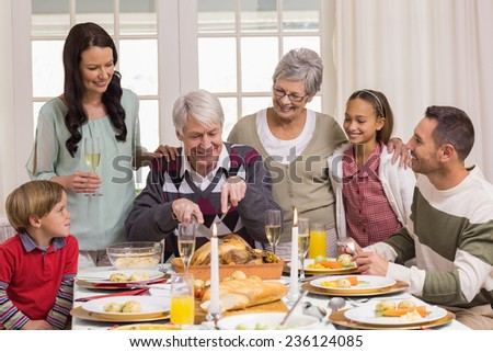 Grandfather carving chicken and his family looking him at home in the living room - stock photo