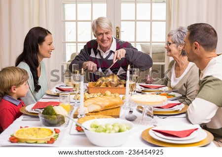 Grandfather carving chicken during christmas dinner at home in the living room - stock photo