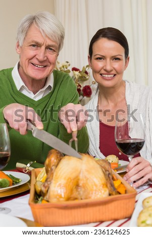 Grandfather carving chicken while woman drinking red wine at home in the living room - stock photo