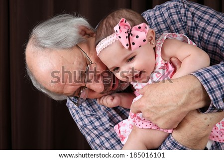 Grandfather cuddling his granddaughter against brown background - stock photo