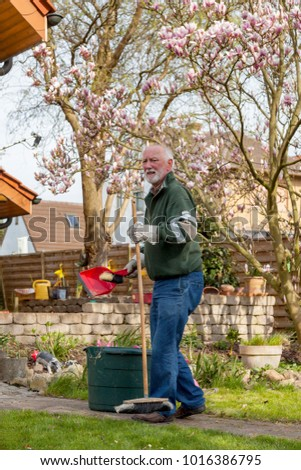grandfather doing some garden work and cleaning the gardden path