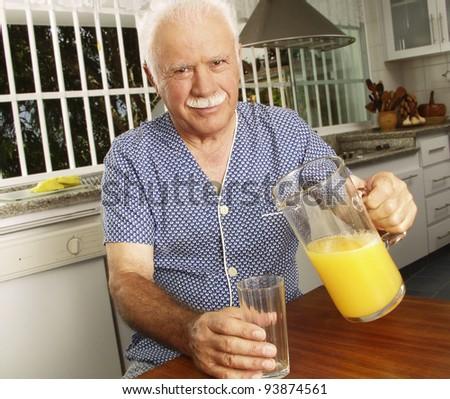 Grandfather drinking orange juice at kitchen. - stock photo