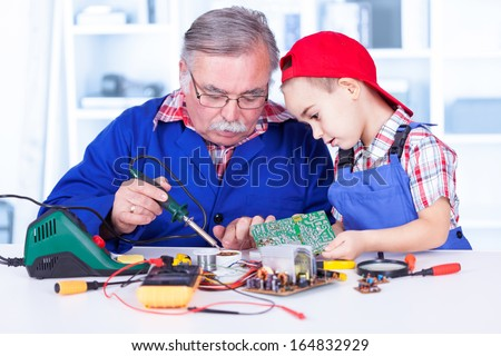 Grandfather explaining to grandchild how soldering works and how to use resin - stock photo