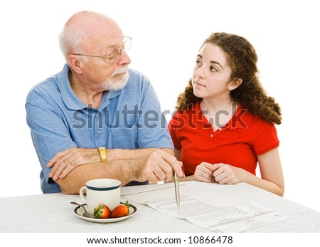 Grandfather explains democracy to his teen granddaughter while filling out his absentee ballot.  Isolated on white. - stock photo