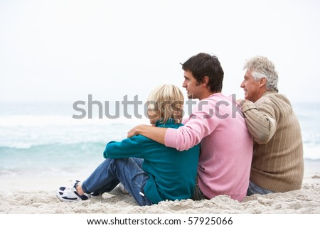 Grandfather, Father And Grandson Sitting On Winter Beach - stock photo