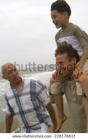 Grandfather, father and son walking on beach - stock photo