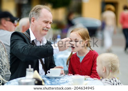 Grandfather feeding frothy milk to his grandchild at summer cafe on beautiful sunny day - stock photo