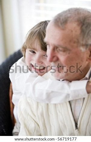 Grandfather getting hug from 9 year old grandson, focus on boy - stock photo
