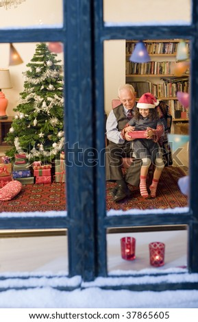 grandfather giving Christmas present to his little granddaughter watched from a snowy window