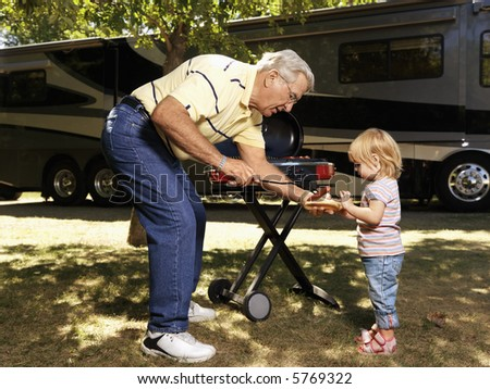Grandfather giving granddaughter hotdog by RV. - stock photo