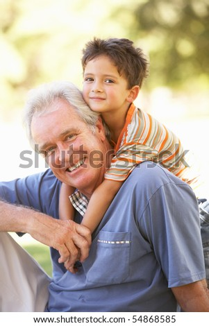 Grandfather Giving Grandson Ride On Back In Park - stock photo