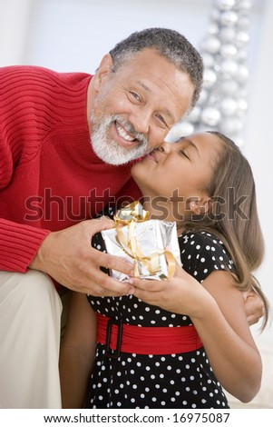 Grandfather Giving His Granddaughter A Christmas Present - stock photo