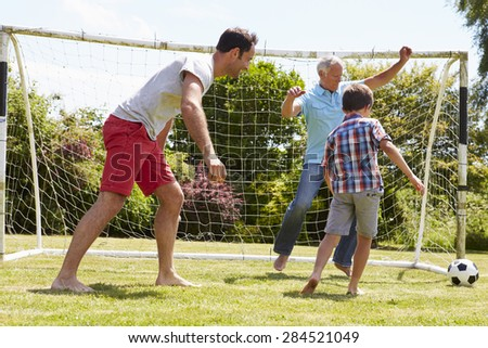 Grandfather, Grandson And Father Playing Football In Garden - stock photo