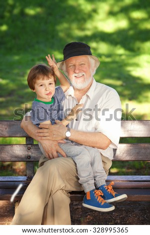 Grandfather having great fun with his grandson in the park - stock photo