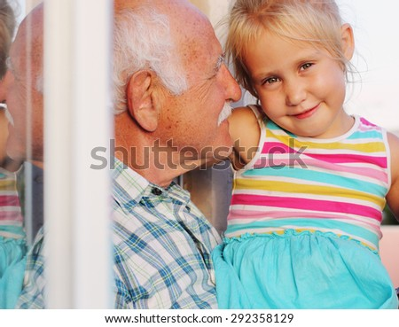 grandfather holding his 4 years old granddaughter - stock photo