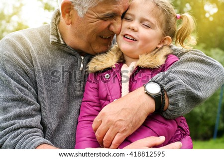 Grandfather hugging granddaughter in the park.   - stock photo