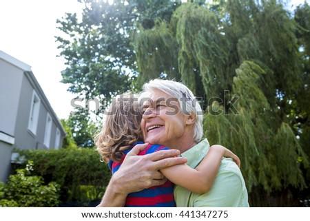Grandfather hugging grandson at back yard - stock photo