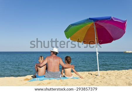 Grandfather hugging his grandson and granddaughter on a beach, looking to the see, back to the camera, colorful umbrella next to them. - stock photo