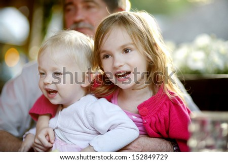 Grandfather hugging his two granddaughters - stock photo