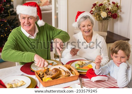 Grandfather in santa hat carving roast turkey at christmas at home in the living room - stock photo