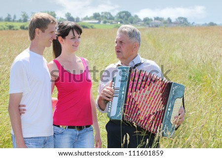 Grandfather in shirt play on accordion, sink for young couple - stock photo