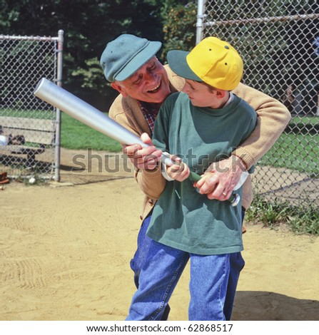 grandfather instructing grandson with baseball bat