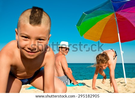 Grandfather is looking with a smile at his grandchildren playing on a sunny beach next to a colorful umbrella. - stock photo