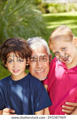 Grandfather laughing outside with two grandchildren in a garden