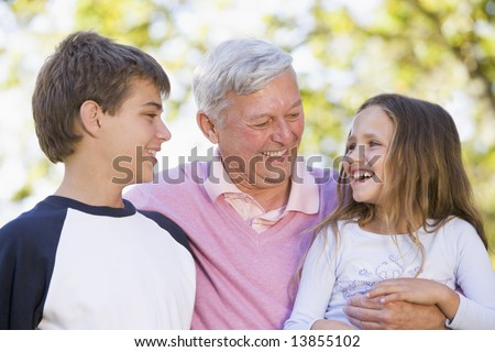 Grandfather laughing with grandchildren - stock photo