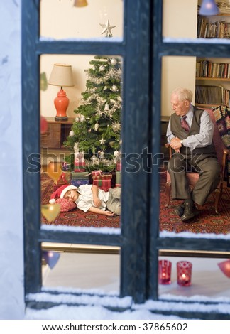 grandfather looking at his asleep grandchild under the Christmas tree. - stock photo