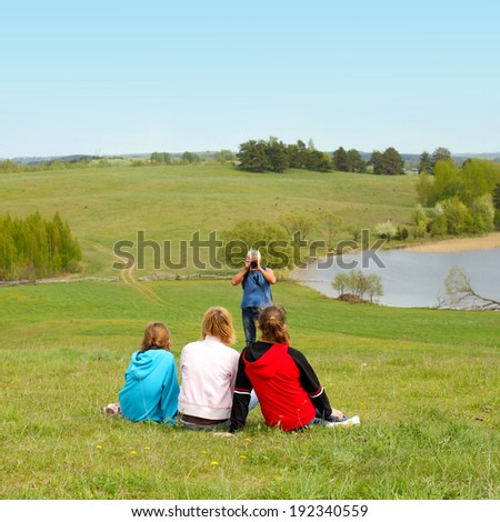 Grandfather photographs his daughter with his granddaughters in a landscape. Family of three generations. Daughter and granddaughter sitting in front of his grandfather, who photographs them - stock photo