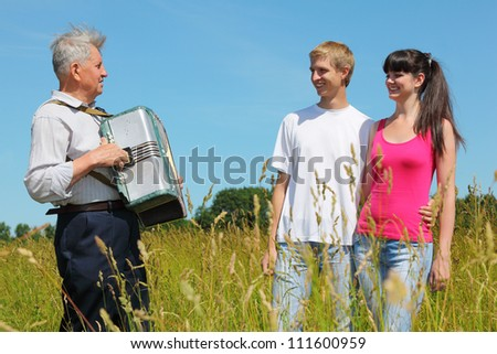 Grandfather play on accordion for young couple in field near wood - stock photo