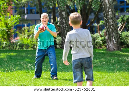 Grandfather Playing American Football Game With Kid In The Park