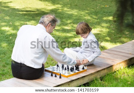 Grandfather playing chess with his grandson in the garden - stock photo